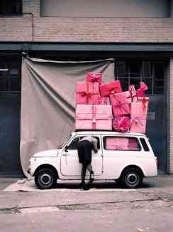 Mulher debruçada na janela de um carro lotado de presentes