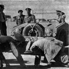 """Um Porsche 597 da primeira geração levado para a Líbia e a legenda original dizia: """"Dois oficiais superiores líbios examinam com interesse os amortecedores dianteiros do 'Jipe' alemão"""" – foto do jornal L'Orient"""