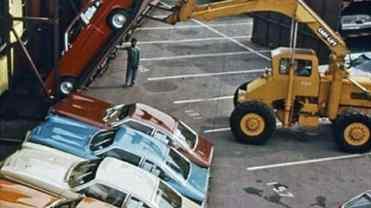 Detalhe da grande empilhadeira elevando a porta com o carro amarrado