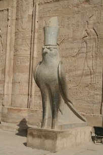 Estátua do deus egípcio Horus. Na parede, sua representação em forma humana