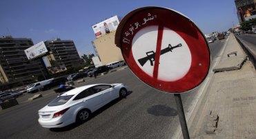 """Uma placa de proibição que mostra um fuzil e uma frase em árabe que significa """"nem de brinquedo"""", na estrada em direção a Beirute, no Líbano (JOSEPH EID/AFP/Getty Images)"""