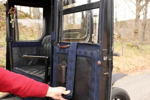 Assim como nos velhos vagões de trem, os vidros das janelas são levantadas e baixadas com uma cinta. O que parece um grande botão de bloqueio é o comando da fechadura da porta