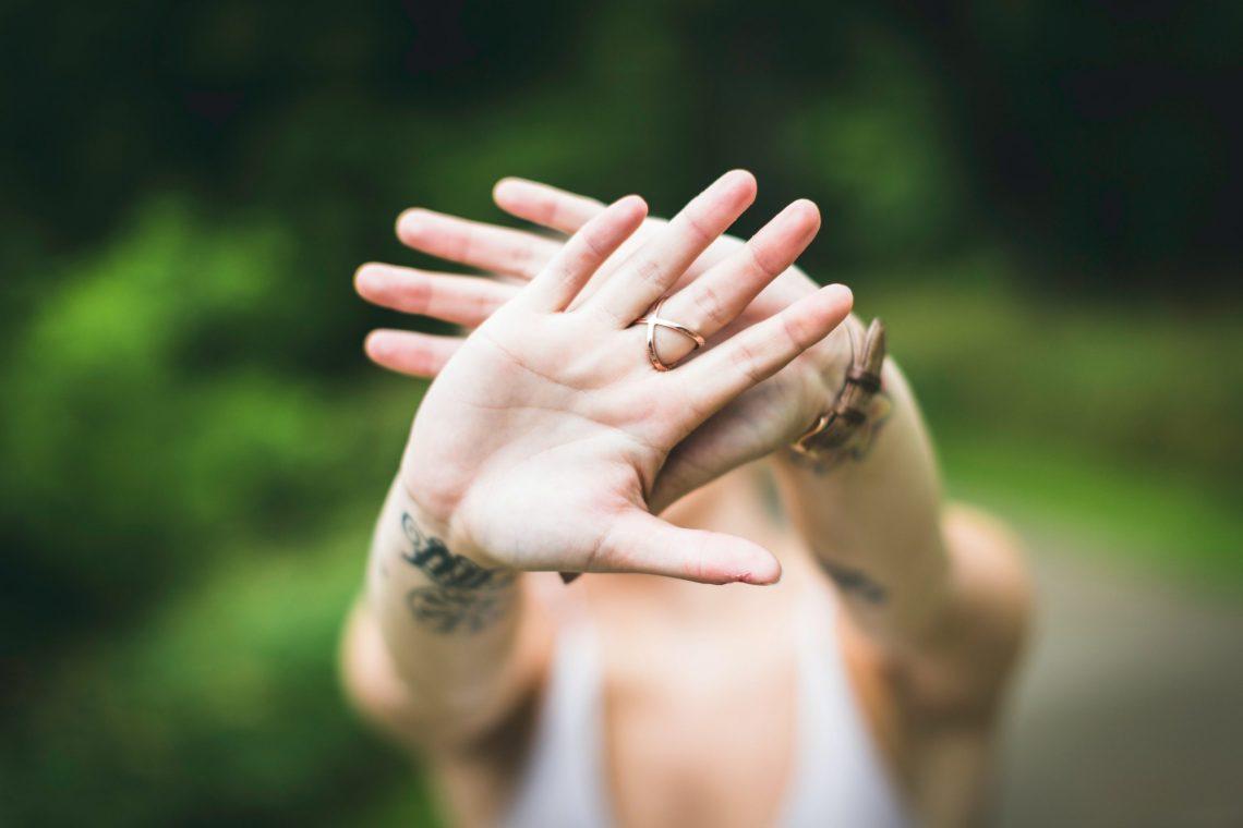 Eine Frau setzt Grenzen mit beiden Händen per Signnal