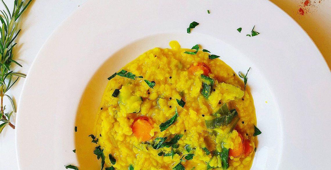Gelbes ayurvedisches Kitchari auf einem weißen Teller mit Kräutern