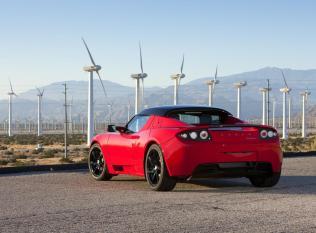 L'arrière d'une Tesla Roadster rouge devant des éoliennes