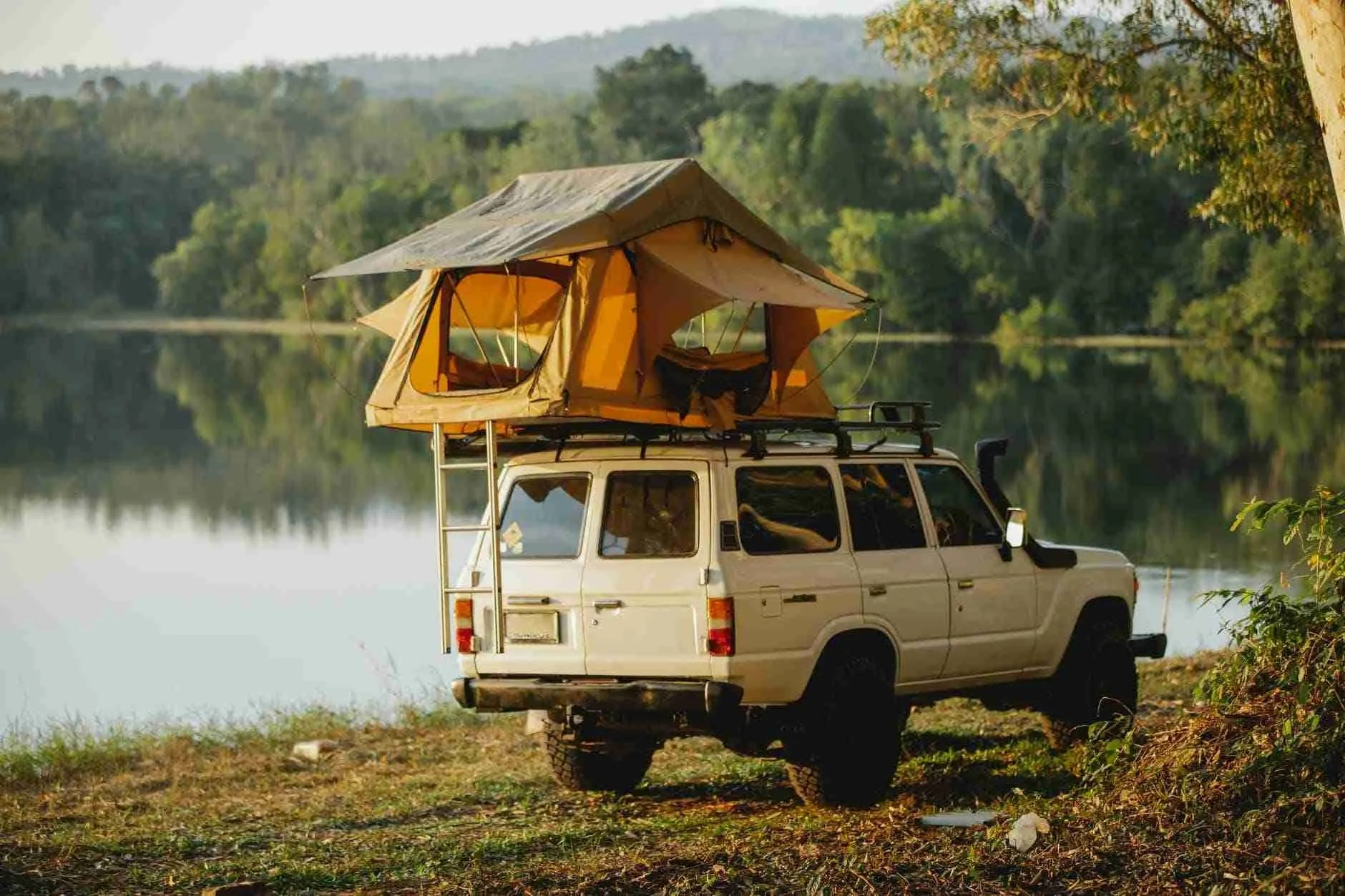 off road car with tent on roof parked on lake shore in forest