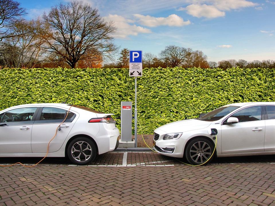Two cars recharging at an EV recharging station.