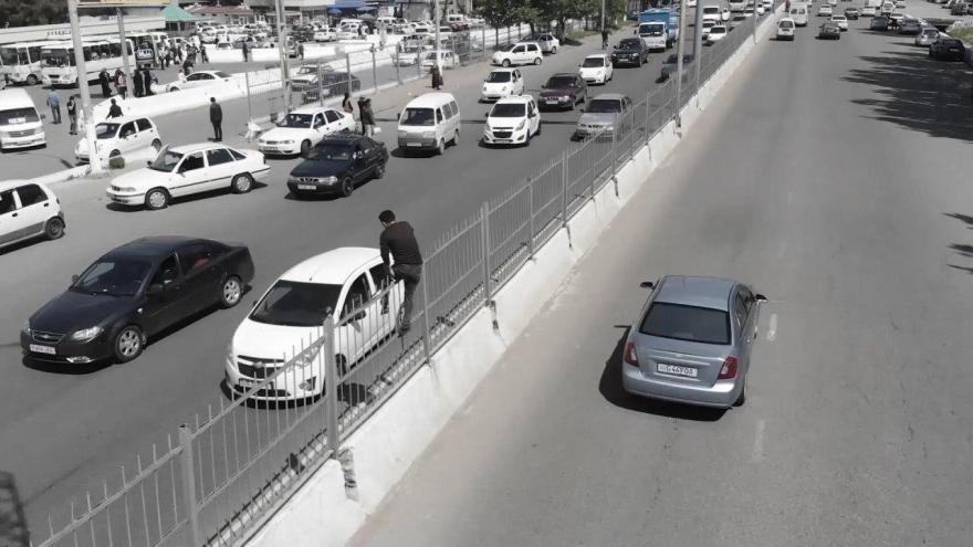 Пешеход перелазит через забор, чтобы перейти дорогу возле базара Ипподром