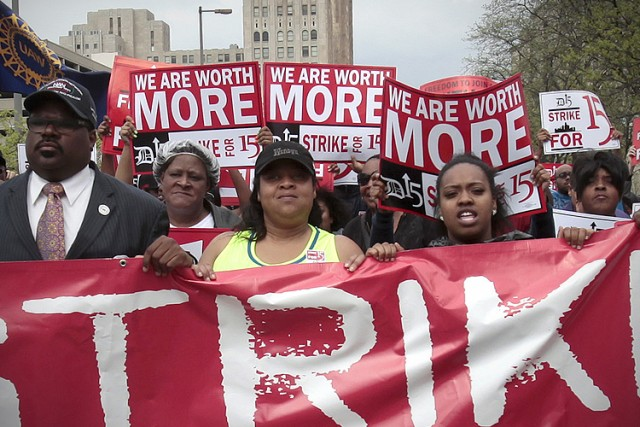 A group of workers and labor activists march down West Grand Boulevard as they demand a raise in the minimum wage for fast food workers in Detroit
