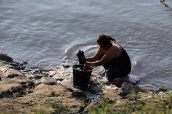 Une femme lave son linge dans le fleuve, tout près des bateaux de croisières à Mandalay - l'autre ailleurs au Myanmar (Birmanie) et Thaïlande, une autre idée du voyage