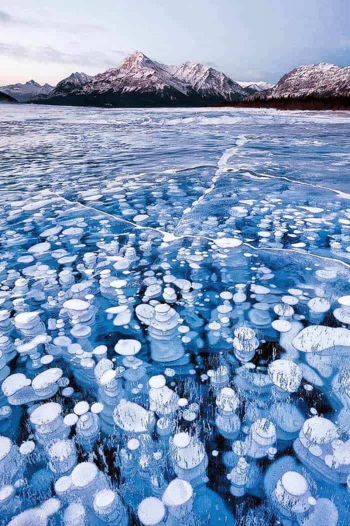 Abraham Lake in Canada! This unique lake has cool-looking bubbles frozen near the surface. The bubbles are full of frozen methane gas, so quite literally a match could set off an explosion. 20 UNREAL Travel Destinations you have to see!! Click through to read the full post!