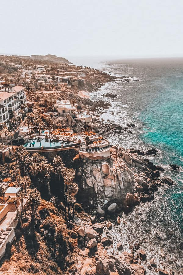 Amazing resorts on the rocky coastline of Cabo San Lucas! Planning a trip to Mexico and wondering which beach vacation you should consider - Cabo or Cancun? If you are wondering which is better than click through to www.avenlylanetravel.com and check out the major differences between the 2 beach destinations in Mexico. #cabo #mexico #cancun #avenlylane #avenlylanetravel