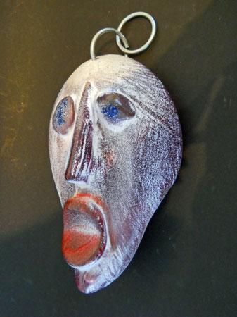 """Masker """"De Schreeuw"""", lengte 25 cm, breedte 19 cm. In de mal gesmolten ingekleurd glas en bewerkt: snijden, slijpen en polijsten."""