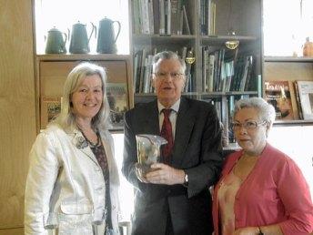 """Annelien van Kempen biedt Chris de Loor het door haar gemaakte geschenk aan, Margriet Pleiter kijkt toe tijdens de opening van """"Landleven Beleven in Glas"""". (bron Veluweland)"""