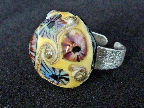 """Nicoline Lenskens, """"Earth"""" verstelbare ring van geborsteld zilver; glastop in aarde-tinten; handgemaakte murrini's en zilveraccentjes; basismaat 18."""