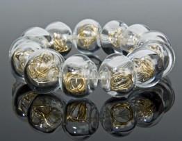 Anat Sapir, armband met transparante glazen kralen met goudendraad inwendig.