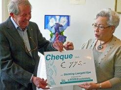 De cheque wordt overhandigd door Margriet Pleiter aan Piet Verhagen.