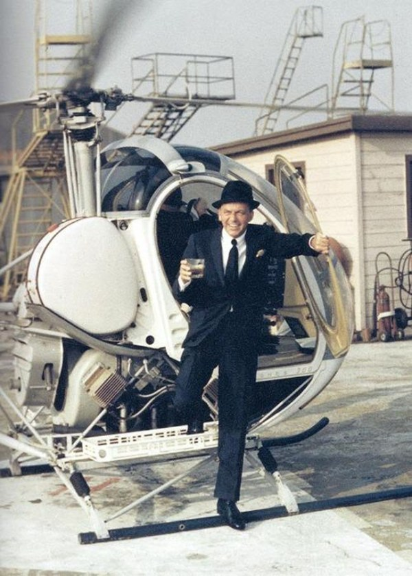 Frank Sinatra stepping out of a helicopter with a drink