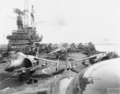 THE FALKLANDS CONFLICT, APRIL - JUNE 1982 (FKD 674) View looking aft down HMS HERMES' flight deck as she sails from Portsmouth for the South Atlantic. Five Sea Harriers of No 800 Squadron Fleet Air Arm are visible on the crowded flight deck. At the time of sailing, the crew had not had time to organise the stowing of aircraft or supplies. Copyright: © IWM. Original Source: http://www.iwm.org.uk/collections/item/object/205190489