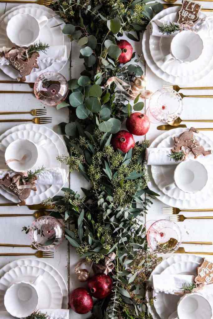 eucalyptus pomegranate running down centre of Christmas theme decorated table