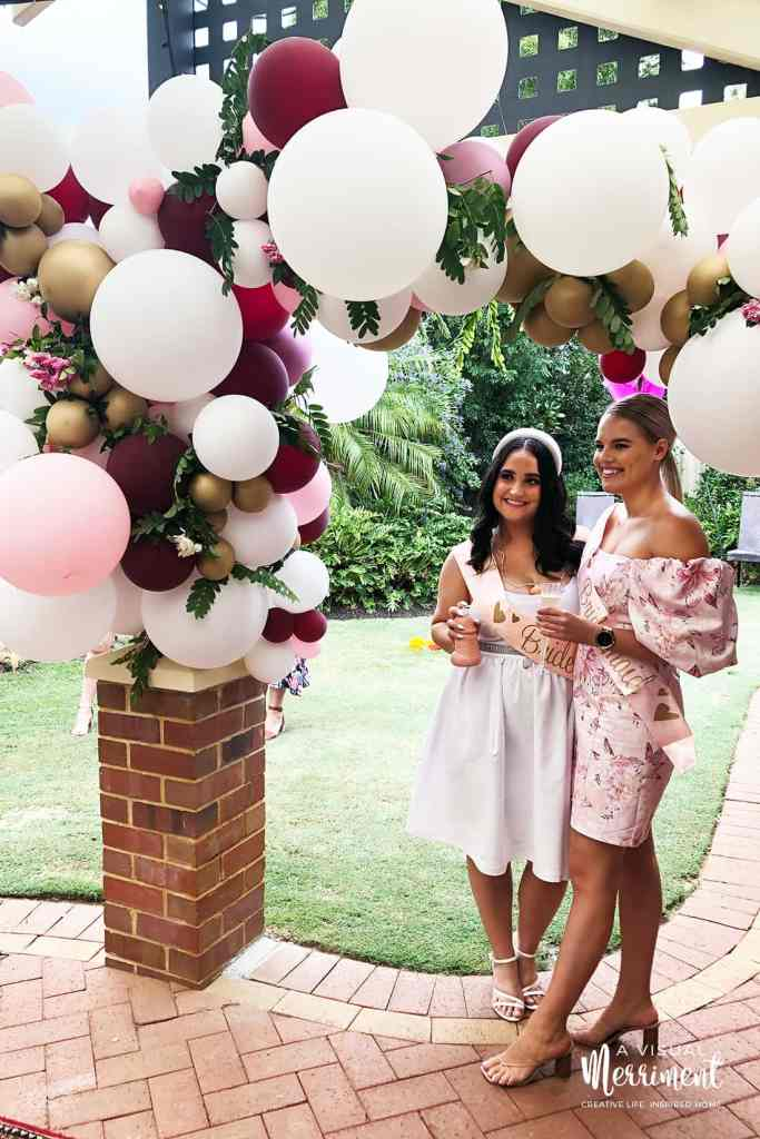 bride and maid standing under balloon arch