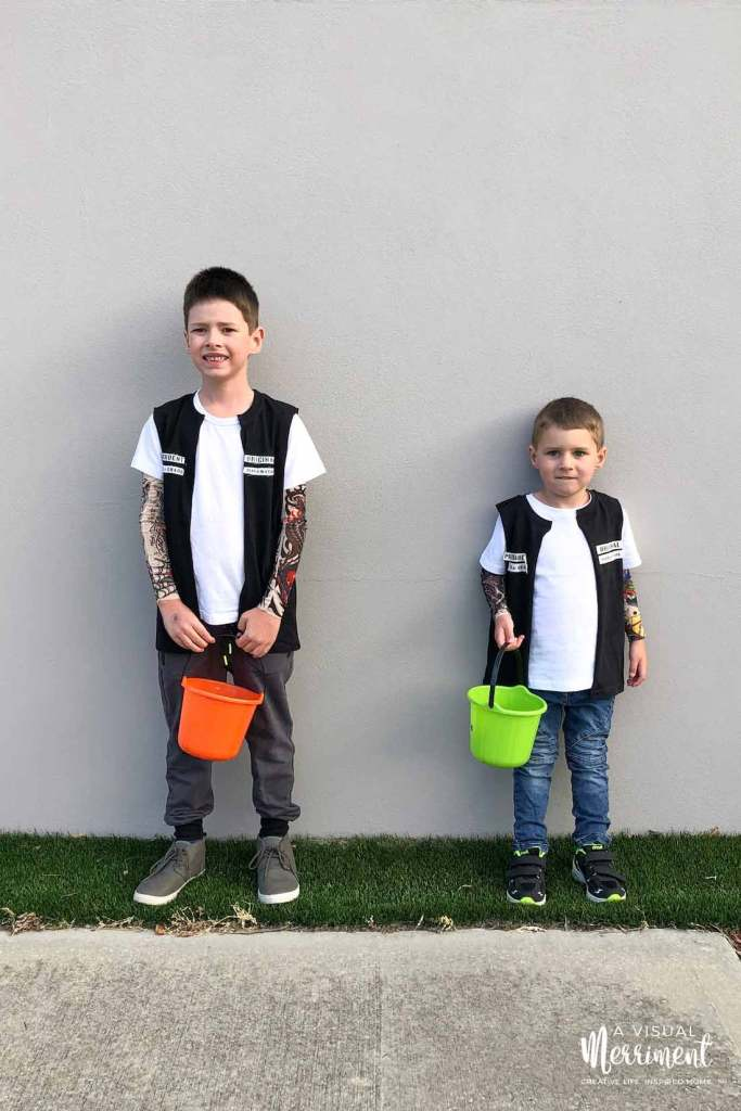two boys in biker costumes with halloween buckets