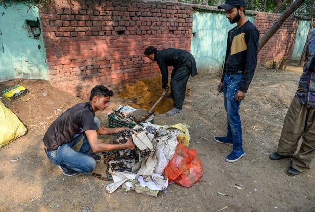 Alcuni saccheggiatori si preparano a bruciare delle copie del Corano prelevate in una moschea