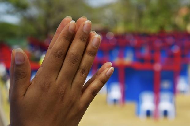 Mani in preghiera: sullo sfondo, i confessionali della Gmg di Panama