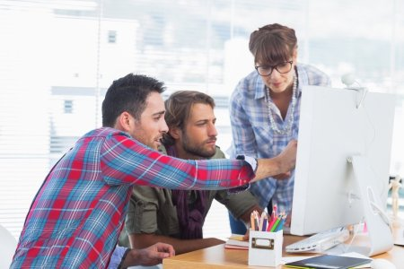 Team of designers working together on a computer.jpeg