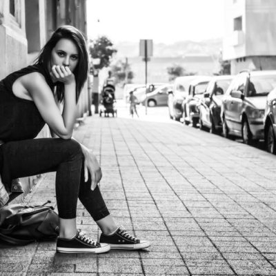 How to be awesome, not perfect. Mental health, wellness, depression, anxiety, stress, burnout, women, woman, awake organics, tips for preventing burnout, how to prevent burnout in women. Woman sitting on sidewalk in busy city. Black and white.