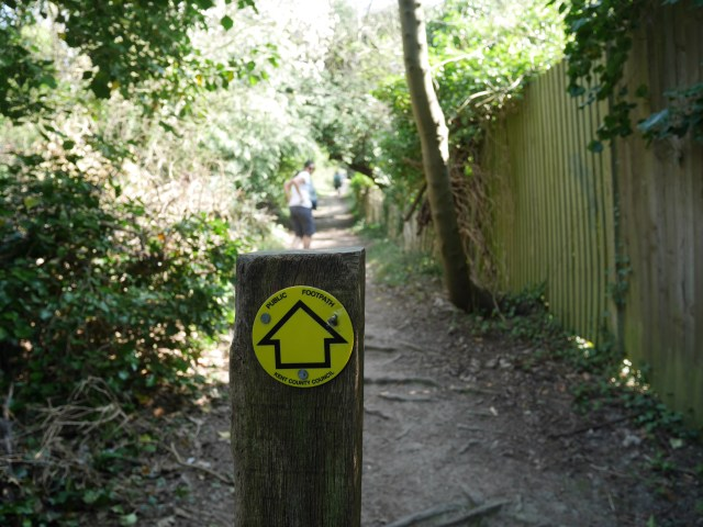 The path starts next to someone's garden fence