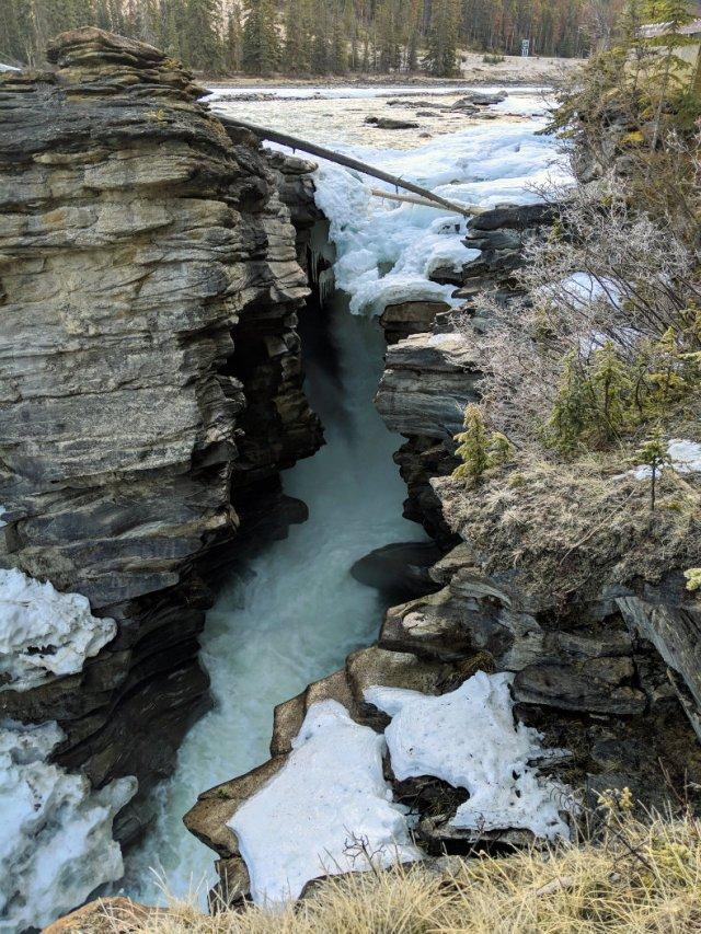 Water swooshing below the frozen falls