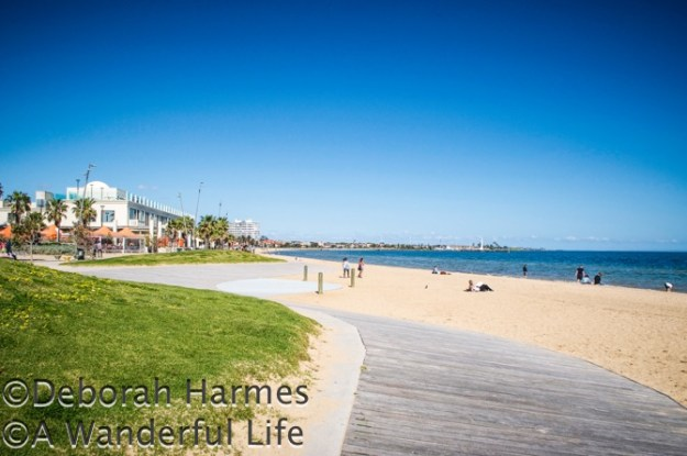 The sparsely populated St. Kilda beach and boardwalk on a sunny Spring day in Melbourne, Australia