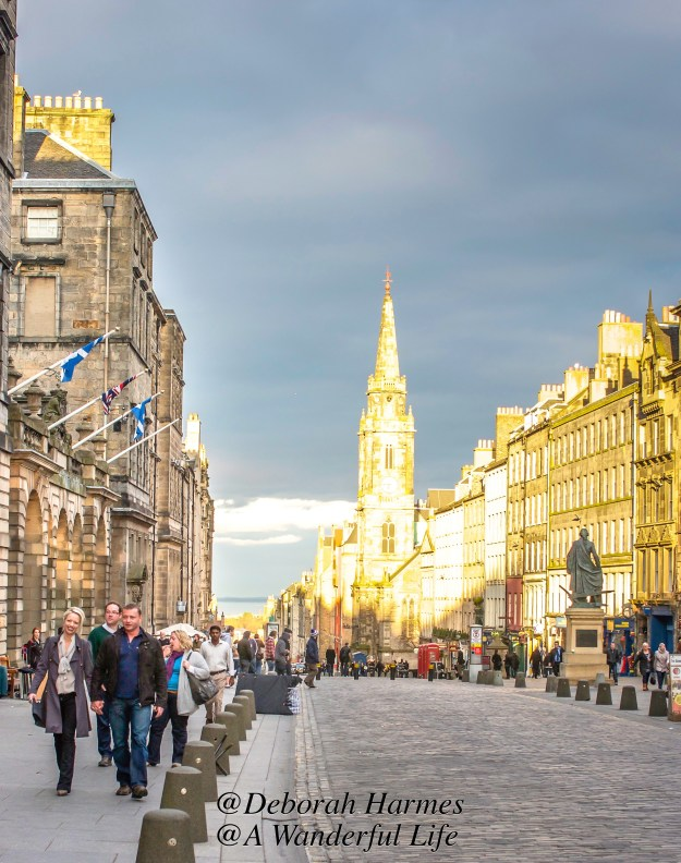 A blast of golden-white light illuminates one end of the Royal Mile in Edinburgh, Scotland on a brisk late-winter day.
