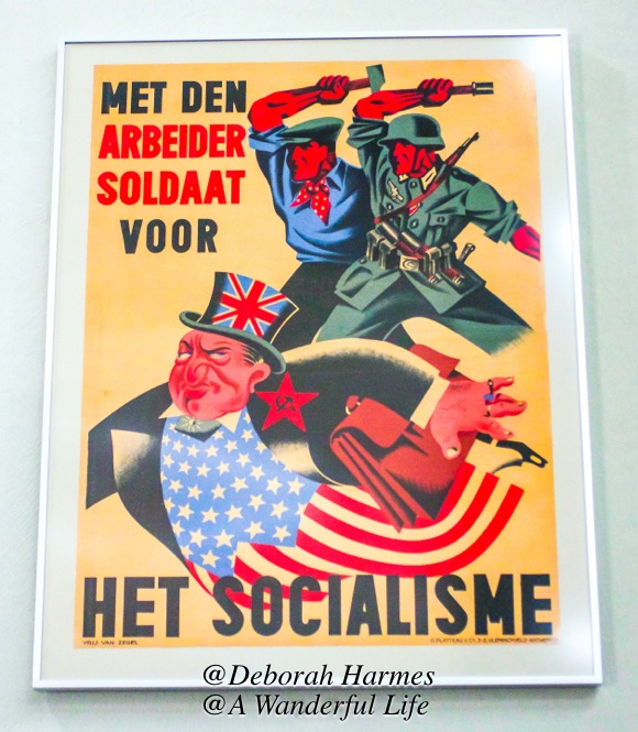 The worker and the soldier are apparently united against Socialism. The red star and Hammer & Sickle symbol on the jacket of the bottom figure reference the Russians aka USSR -- Union of Soviet Socialist Republics. And that same figure has clothing that references the stars and stripes of the USA and a top hat with the British flag on it. Interesting political statement!