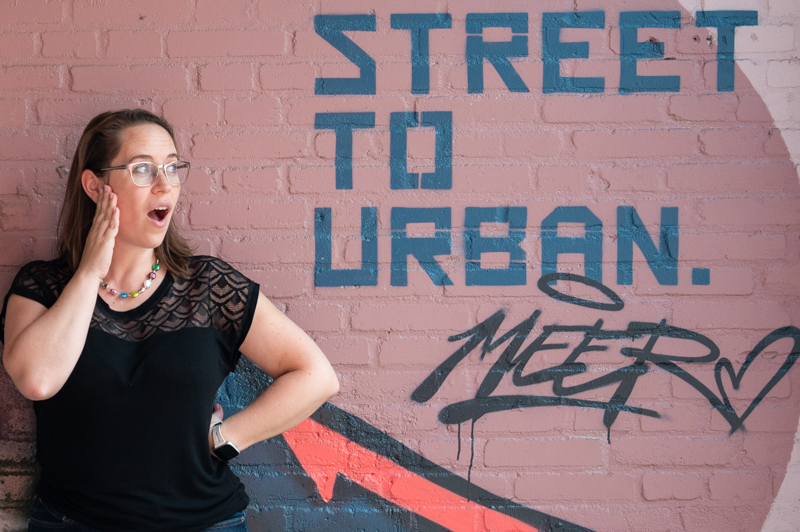 """Jessica in black shirt in front of a wall mural that says """"street to urban"""""""