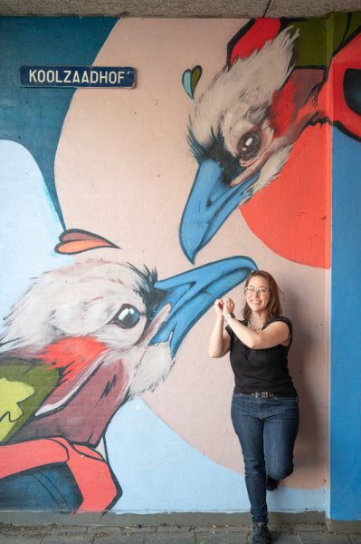 Jessica in front of street art mural with birds painted on it