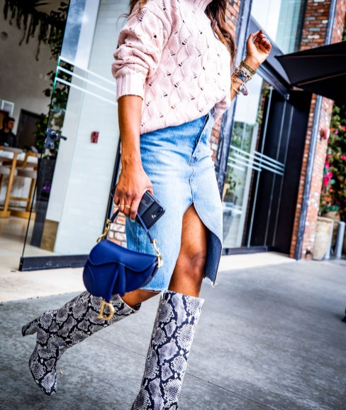 Atlanta fashion blogger Monica Awe-Etuk wearing a pink chunky knit sweater, snakeskin boots, denim midi skirt, dior saddle bag, square gucci sunglasses and pink fedora at the Dream Hollywood Hotel in LA