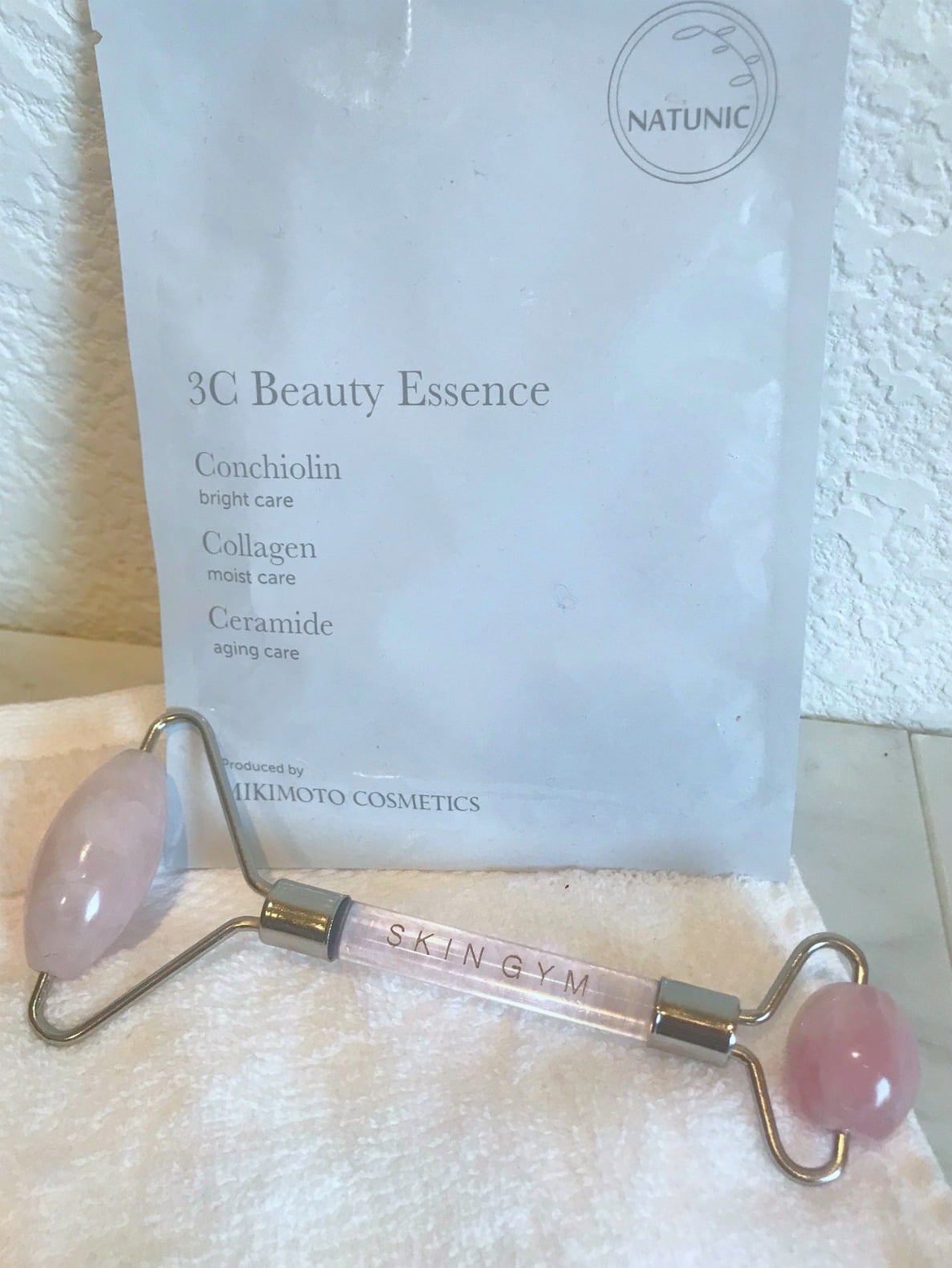 rose quartz roller and sheet mask on a well styled life