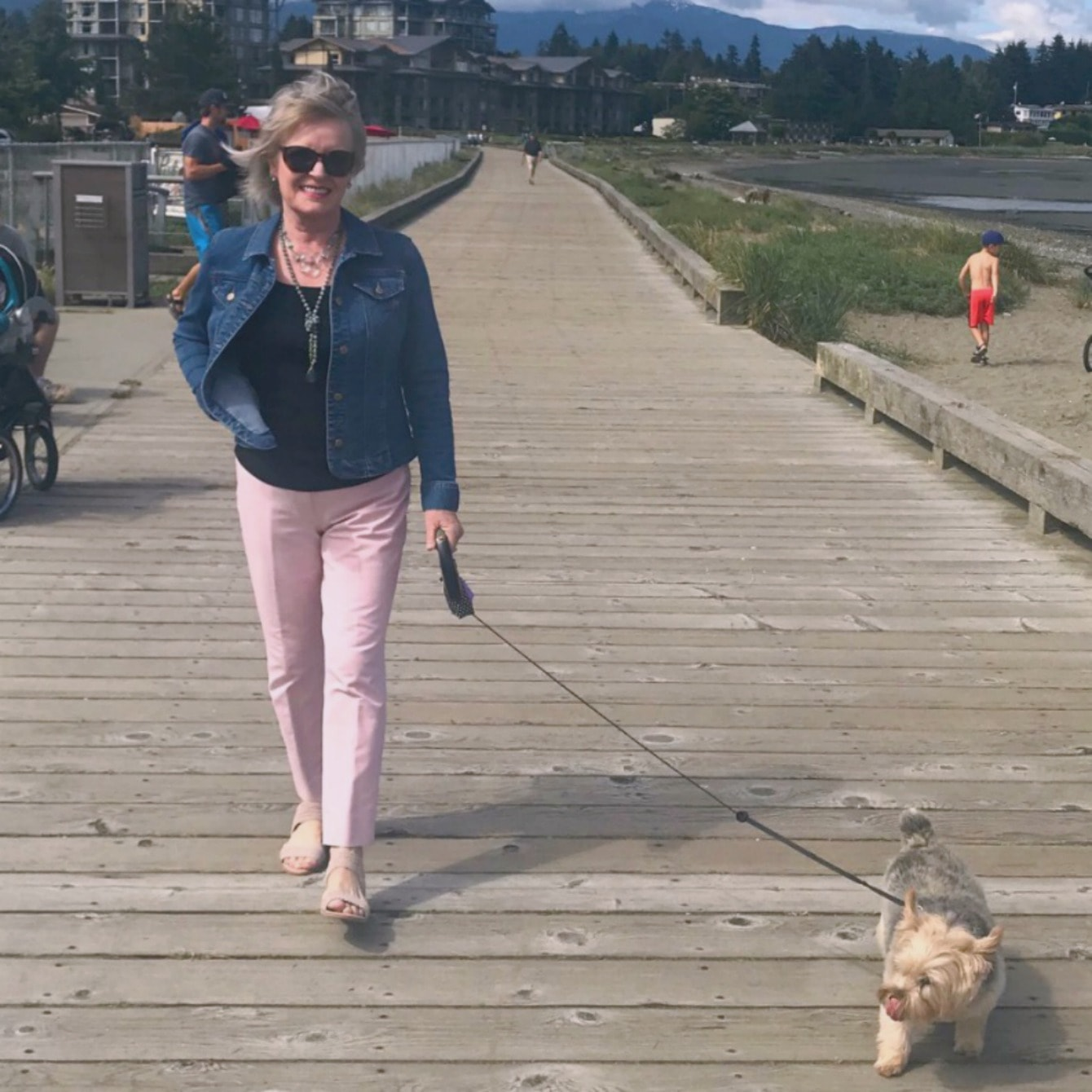 Jennifer from A Well Styled Life wearing bluye denim jacket, pink pants and taupe flat sandals