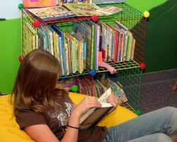 Language learning strategy reading: A girl reading a book on a beanbag chair.