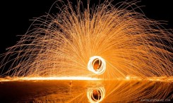 Awesomeness and reflections while a local dances some steel wool by the beach in Koh Tao, Thailand after sunset.