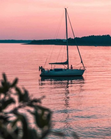 Yacht and pink sunset on a Pula bay in Croatia