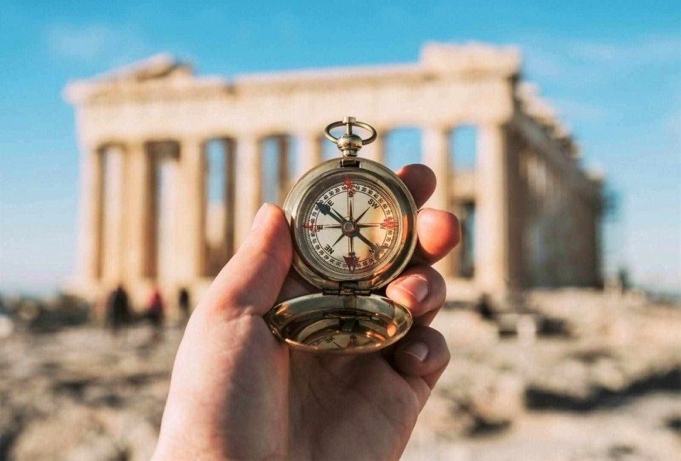 Compass held by a hand in front of the Parthenon - Places to visit in Athens Greece
