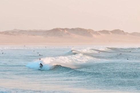 Surfers at sunset in Praia de Dunas, Baleal