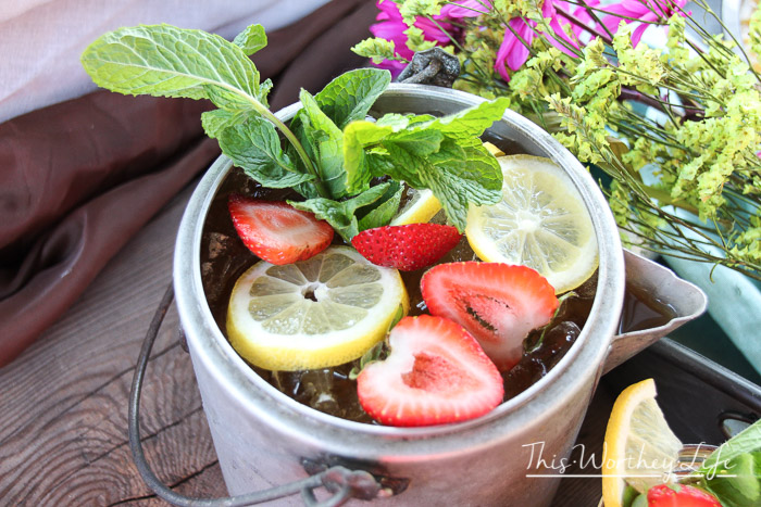 Cool down this summer with our summer tea cocktail. This adult iced tea is filled with strawberries, lemon, Jack Daniels, and mint. Plus, making it in a kettle is an extra bonus! Get the recipe below!