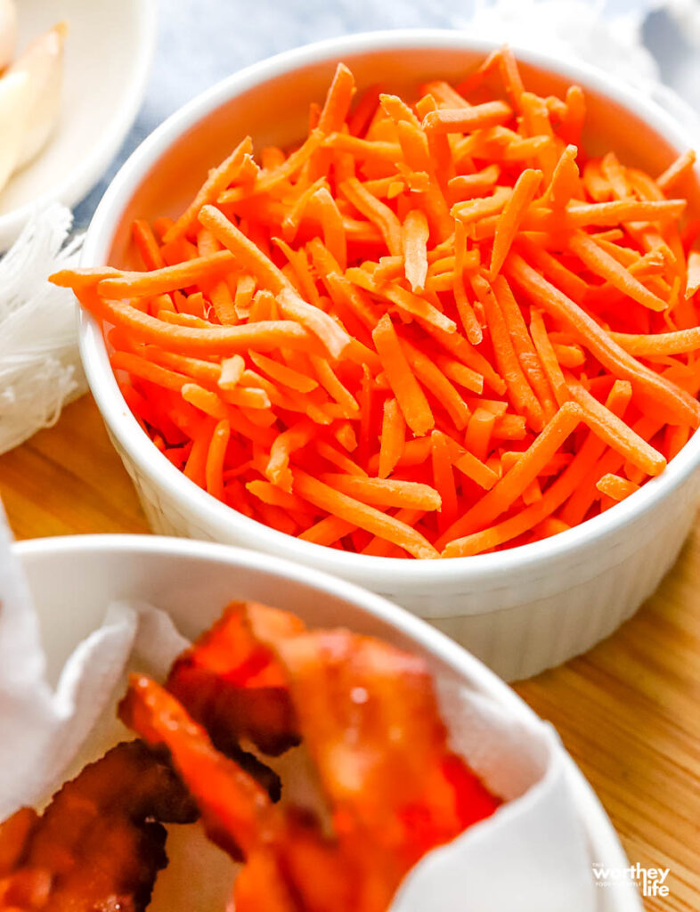 fresh shredded carrots in a white small bowl