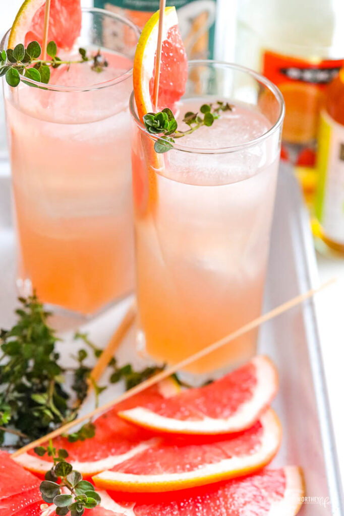 fruit gin cocktail with two glasses and fresh grapefruit