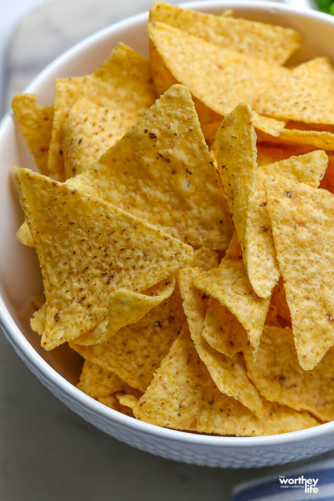 a large white serving bowl filled with corn tortilla chips