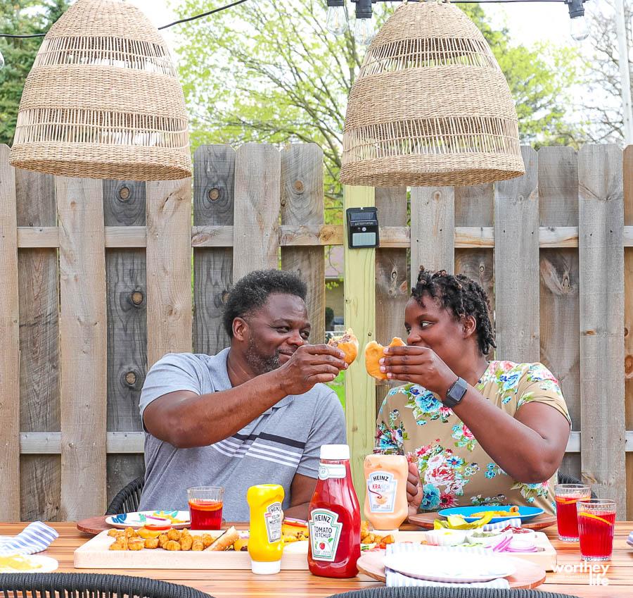 couple enjoying grilled burgers outside